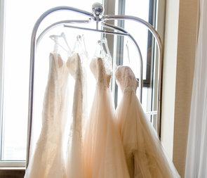Hier zu sehen sind vier Brautkleider auf Bügeln an einer Garderobe.