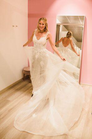Hier zu sehen ist eine Braut in Berlin. Sie trägt ein Brautkleid mit Herzausschnitt und Spitze und steht auf einem Balkon. Im Hintergrund ist die Berliner Gedächtniskirche zu sehen.
