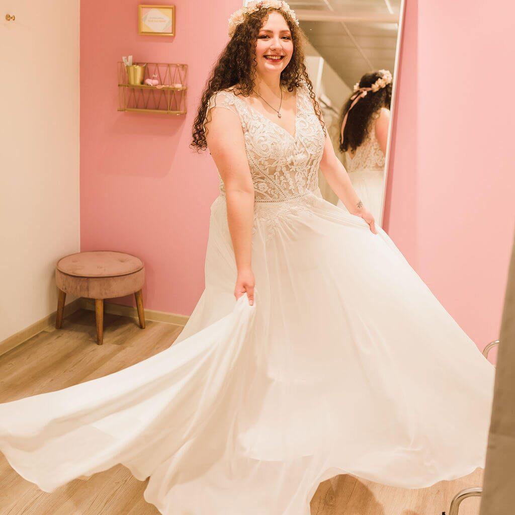 Brautkleid von Sincerity Bridal mit Spitze und Carmenträgern. Zu kaufen im großen Brautladen Princess Dreams in Berlin.