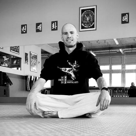 Personal Trainer Axel Schulze sitzt im Schneidersitz in seinem BUDOSPORT.CLUB Jena auf dem Boden