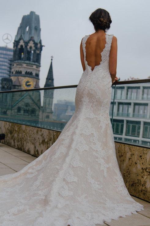 Eine Braut am Geländer in einem Fit and Flare Kleid von St. Patrick Bridal. Im Hintergrund ist Berlin zu sehen. Das Brautkleid lässt sich im großen Brautmodengeschäft Princess Dreams in Berlin kaufen.